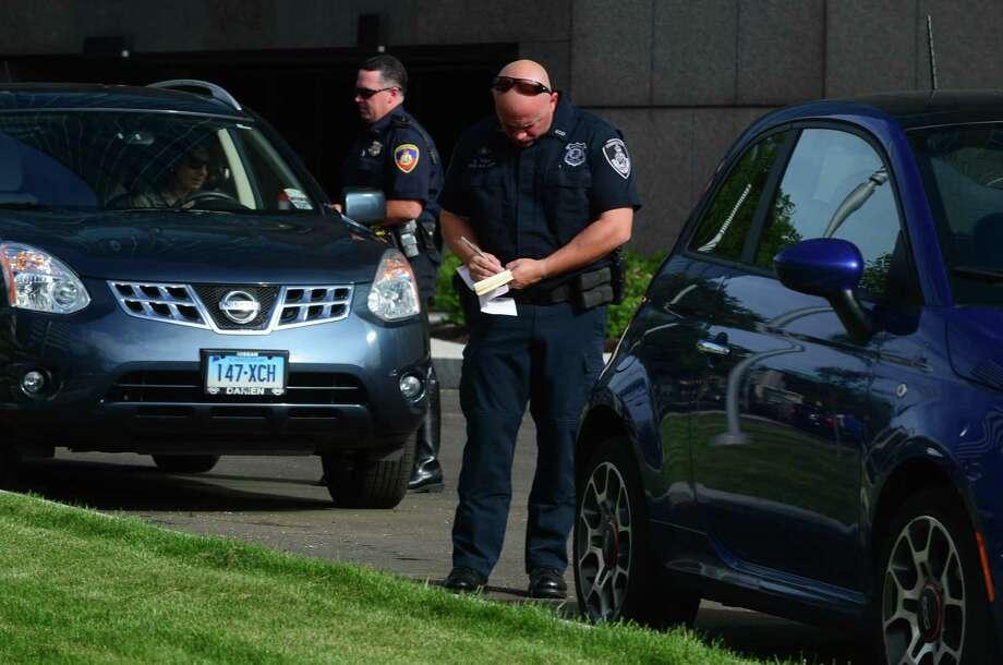 Officer Erin Drew, center, and The Stamford Police Department write tickets in Stamford, Conn., in 2014. Photo: Erik Trautmann / Hearst Connecticut Media / Norwalk Hour