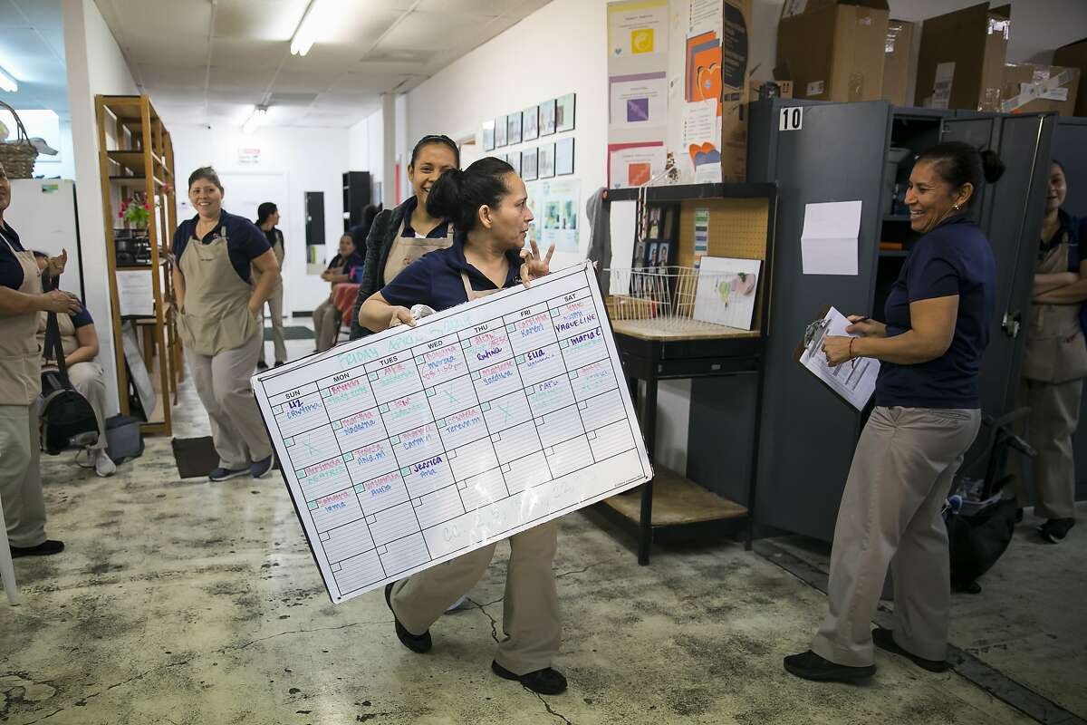 A white board with the day's assignments is posted during morning deployment on Friday, April 5, 2019, at Maid Brigade, a residential cleaning service in Gulfton.