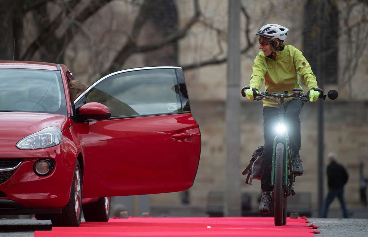 27 March 2019, Baden-Wuerttemberg, Stuttgart: During a safety training course for pedelec drivers, a woman drives past a car that opens the door. Photo: Marijan Murat/dpa (Photo by Marijan Murat/picture alliance via Getty Images)