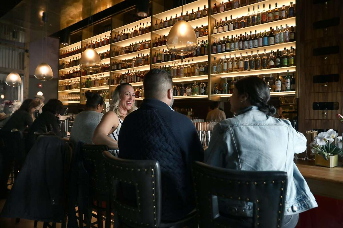 Hi'iaka Ambrose (middle)Brent D. Sanchez (second from left), and Tatiana Feijou (right) have drinks at Niku on Wednesday, March 27, 2019, in San Francisco, Calif.