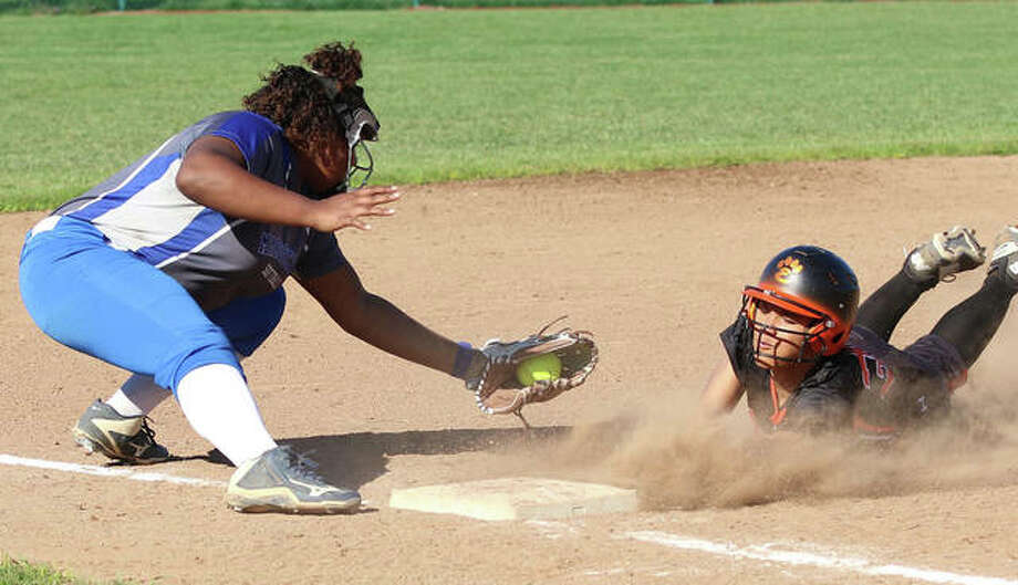 Edwardsville's Maria Smith (right) avoids the tag from Marquette Catholic third baseman Kyra Green while diving in safely to get first from to third on a sacrifice bunt in the third inning Monday at Edwardsville. Photo: Greg Shashack / The Telegraph