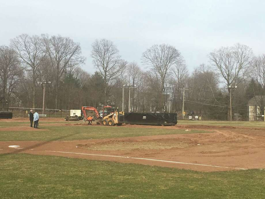 Ridgefield town officials examine the damage done to Ciuccoli Field Sunday afternoon. On Saturday, 25 gallons of gasoline were poured onto the infield and lit on fire to make the field playable for the Ridgefield High School baseball team. A certified emergency response company that specializes in hazardous waste removal dug up six to eight inches of soil from the infield Saturday into Sunday. The town hopes to have new soil placed on the field Tuesday with the team returning to action late next week or next weekend. The police are investigating the incident. Photo: Stephen Coulter / Hearst Connecticut Media