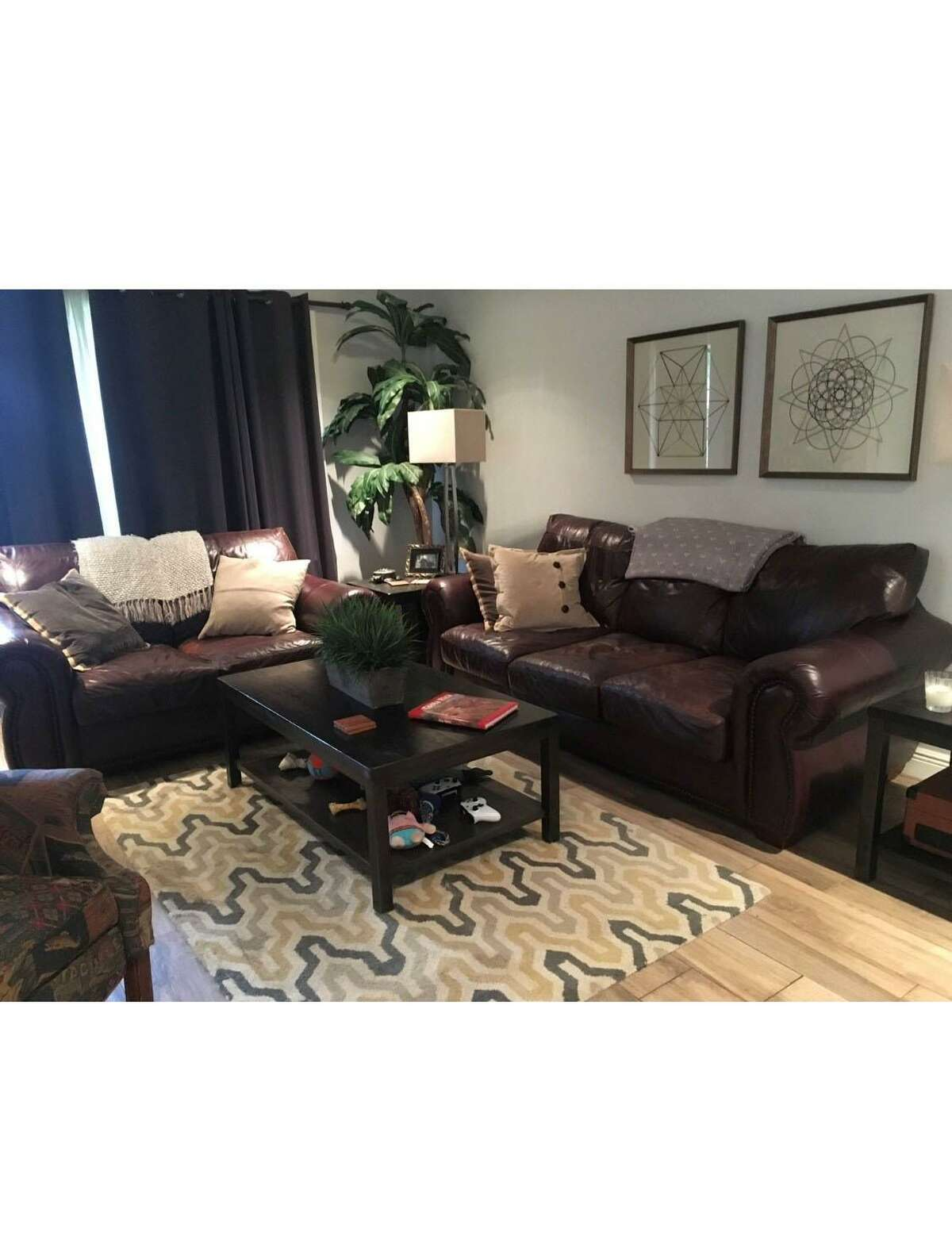 Before: Dobbs' living room featured dark leather sofas and dark accent tables. The accent rug was too small for the space.