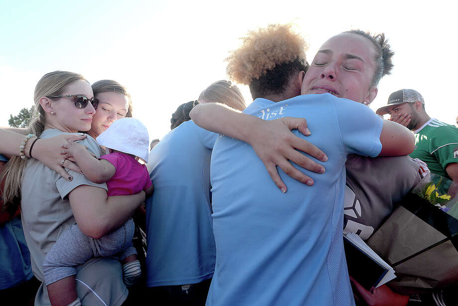 Bethany Cherry Keeling with daughter Keris is consoled by young soccer players while Grace Richard (right) and Alyssa Vallier hug during the vigil in honor of soccer coach and Nederland graduate Rico Keeling, 29, who passed away unexpectedly at his home Sunday night. Keeling was a coach and trainer to many youth soccer players throughout the area. Many of them, along with family and friends gathered at the Cris Quinn Soccer Complex for the memorial Monday. Photo taken Monday, April 8, 2019 Kim Brent/The Enterprise Photo: Kim Brent/The Enterprise