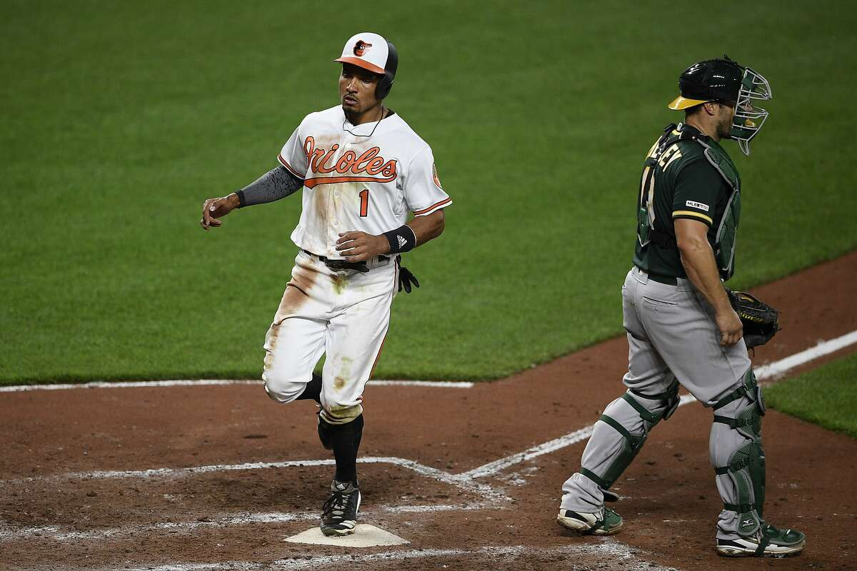 Baltimore Orioles' Richie Martin, left, comes in to score on a sacrifice fly by Cedric Mullins during the sixth inning of a baseball game as Oakland Athletics catcher Josh Phegley, right, looks on Monday, April 8, 2019, in Baltimore. (AP Photo/Nick Wass)