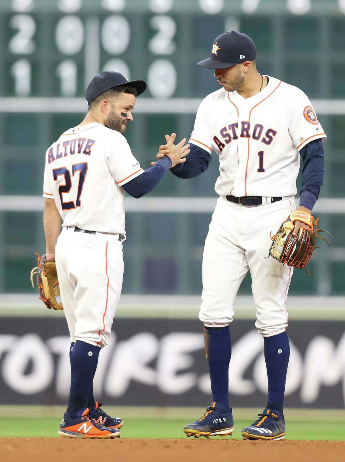 Houston Astros second baseman Jose Altuve (27) and Houston Astros shortstop Carlos Correa (1) celebrate the team's 4-3 win over New York Yankees at Minute Maid Park on Monday, April 8, 2019 in Houston. Astros won the game 4-3 and lead the series 1-0.