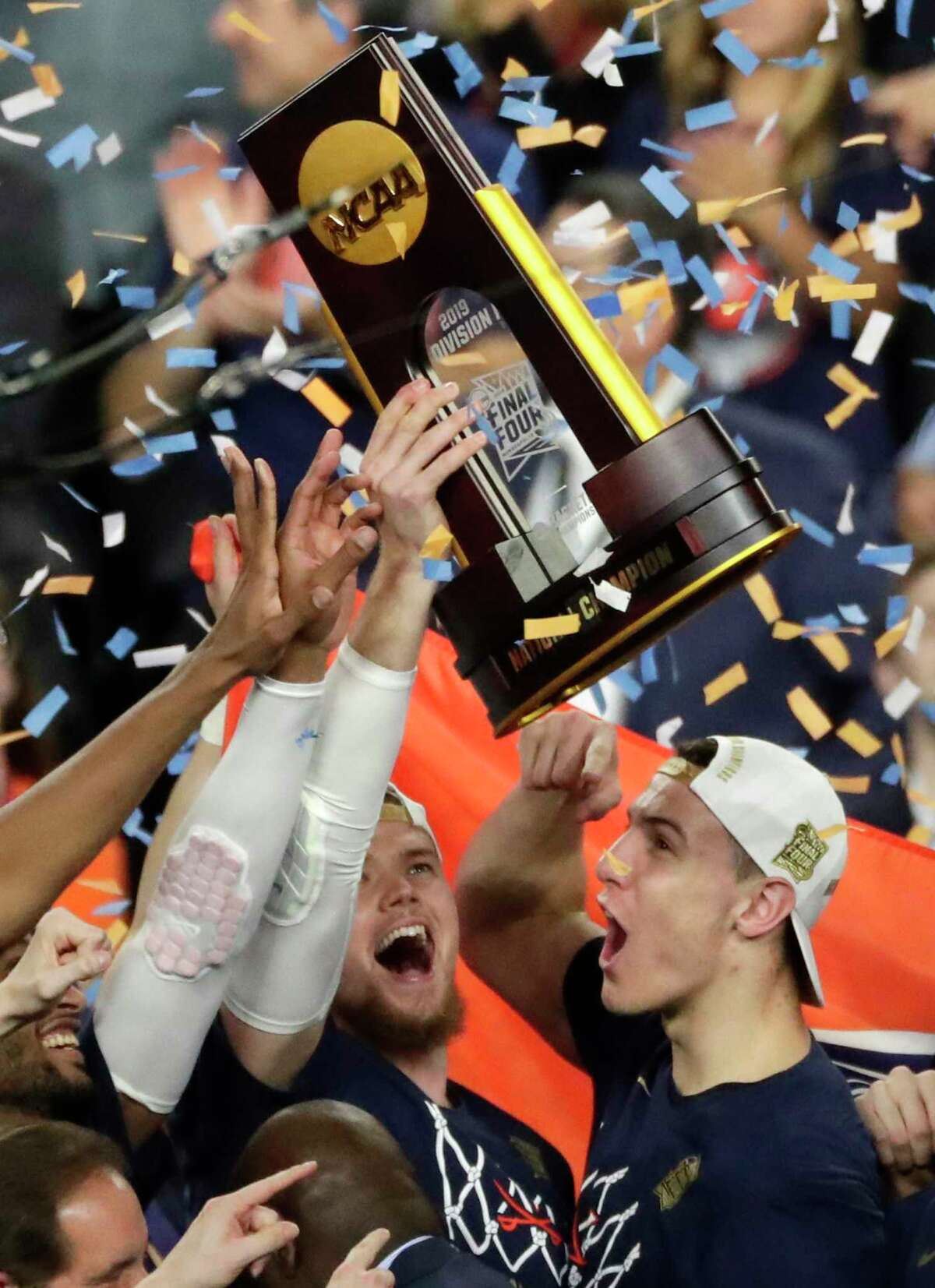 Virginia players celebrate with the trophy after defeating Texas Tech 85-77 in the championship game in the Final Four NCAA college basketball tournament, Monday, April 8, 2019, in Minneapolis. (AP Photo/Matt York)