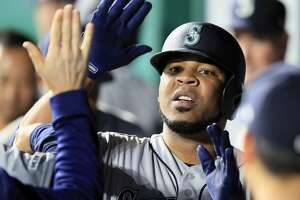 Seattle Mariners' Edwin Encarnacion is congratulated by teammates after his solo home run during the sixth inning of a baseball game against the Kansas City Royals at Kauffman Stadium in Kansas City, Mo., Monday, April 8, 2019. It was the first of two home runs in the inning for Encarnacion. (AP Photo/Orlin Wagner)