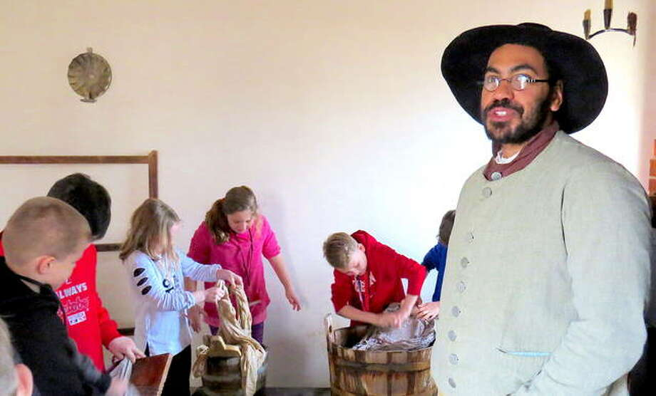 Stephenson House Assistant Director Jeffrey Edison teaches students from Woodland Elementary School about laundry and other household chores while the students washed some clothes during a recent hands-on field trip. Photo: For The Intelligencer