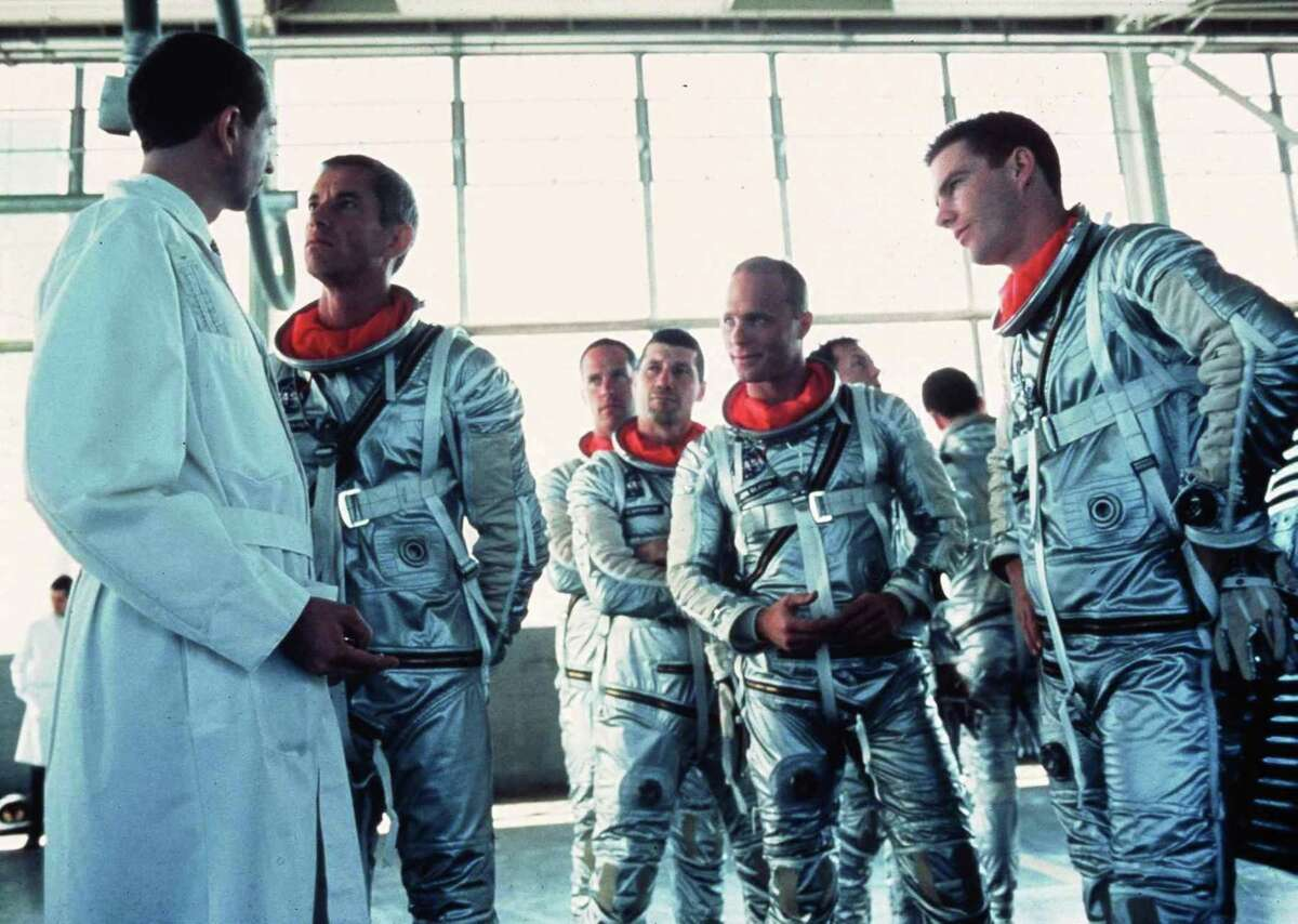 """In a scene from the 1983 film """"The Right Stuff,""""Alan Shepherd, played by Scott Glenn, second left, confronts a NASA scientist about changes to the Mercury capsule while the other astronauts, from center left, Scott Carpenter, played by Charles Frank, Gus Grisson, played by Fred Ward, John Glenn, played by Ed Harris, and Gordon Cooper, played by Dennis Quaid, provide moral support."""