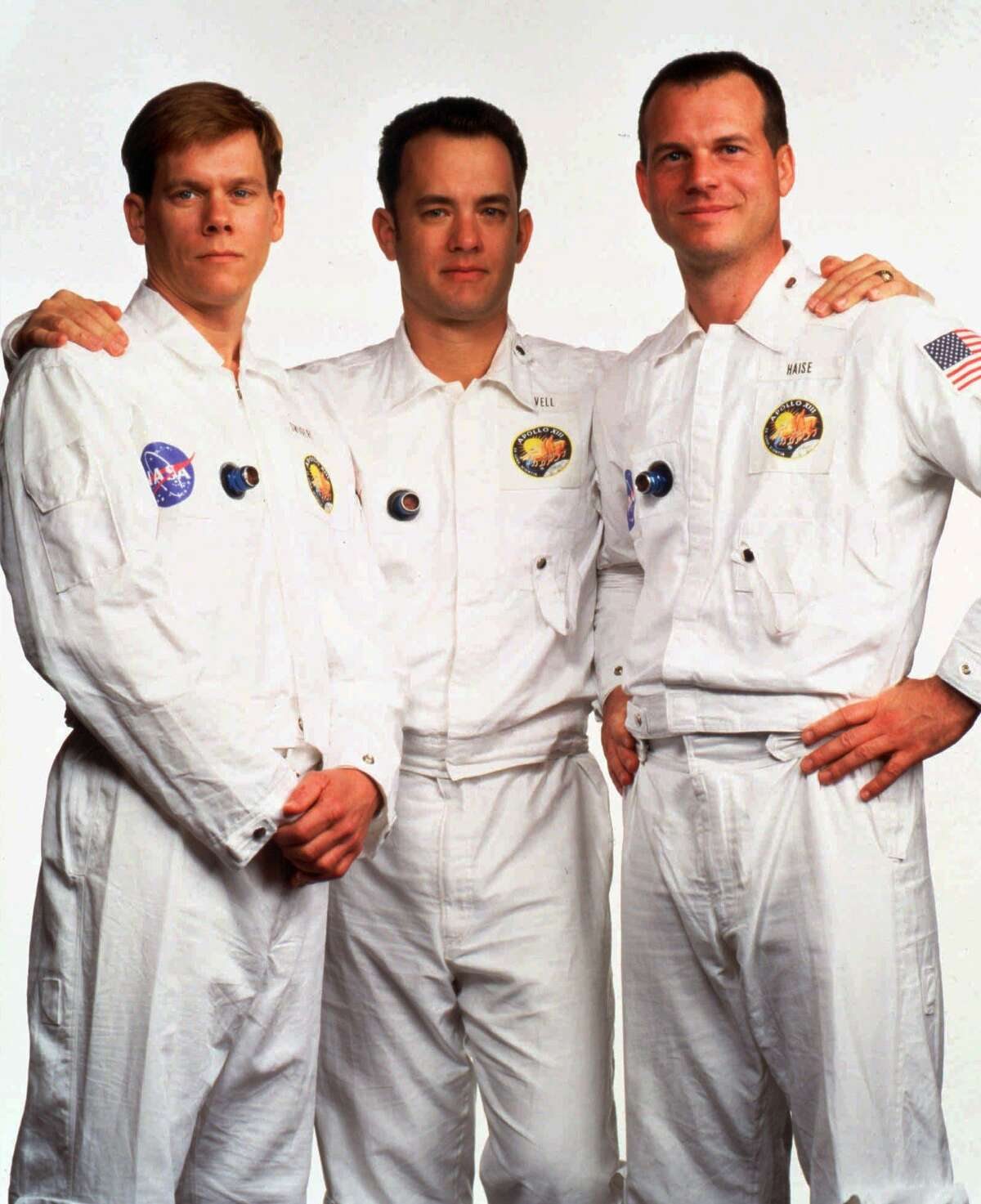 """Tom Hanks, center, poses with fellow actors Kevin Bacon, left, and Bill Paxton in flight suits for the movie """"Apollo 13,"""" directed by Ron Howard, which tells the story of the ill-fated 1970 moon shot."""