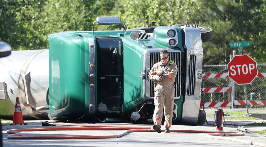 Members of the Houston Hazardous Materials Response team try to contain a spill from a big rig that flipped over on its side, at 6th and Rutland, in the Hieghts, Tuesday, April 9, 2019, in Houston. The wreck happened around 5:45 a.m. Residents in the area were asked to evacutate, while crews worked to contain the leak. Photo: Karen Warren, Staff Photographer / © 2019 Houston Chronicle