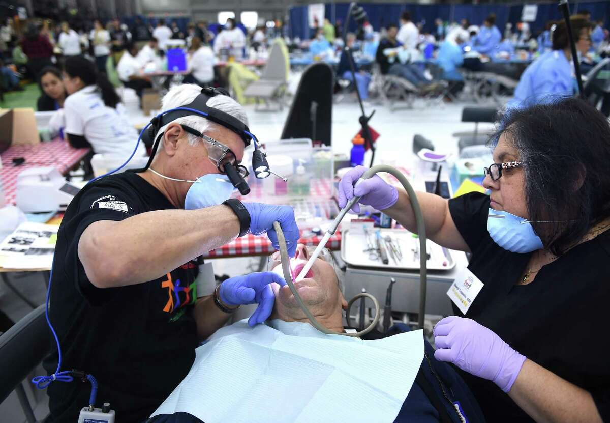 Frank Bensavage, center, of North Branford, gets a filling from dentist Gerald Alexander, left, of New Haven, and dental assistant Cheryl Cappello at the Connecticut Mission of Mercy Free Dental Clinic in New Haven in 2017.