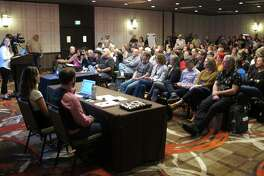 In this Monday, April 8, 2019, photoHolly Prohaska, at podium left, a project manager for a Bureau of Land Management contractor that helped prepare a draft environmental impact statement for the Burning Man festival, describes the document during a public hearing in Sparks, Nev. Nearly 200 Burning Man backers packed a casino meeting room to mostly complain about new conditions and restrictions the government wants to place on the counter-culture festival in the northern Nevada desert.