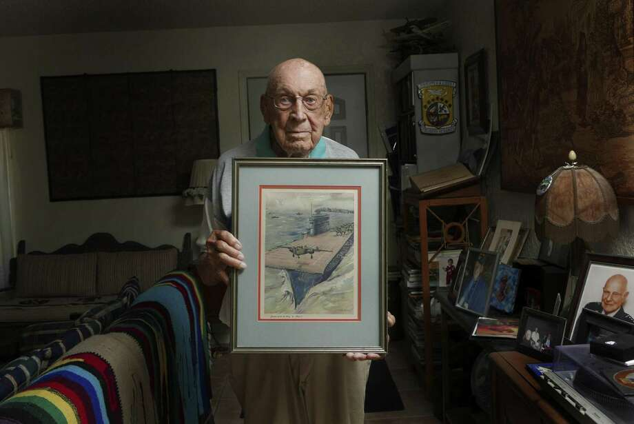 Retired Air Force Lt. Col. Dick Cole holds an image of a B-25 bomber that he copiloted taking off from the deck of the carrier USS Hornet on April 18, 1942. Cole was copilot to Jimmy Doolittle on that day in World War II when 16 B-25 bombers flew off the deck of the carrier to bomb Japan. Photo: Billy Calzada, Staff / San Antonio Express-News / San Antonio Express-News