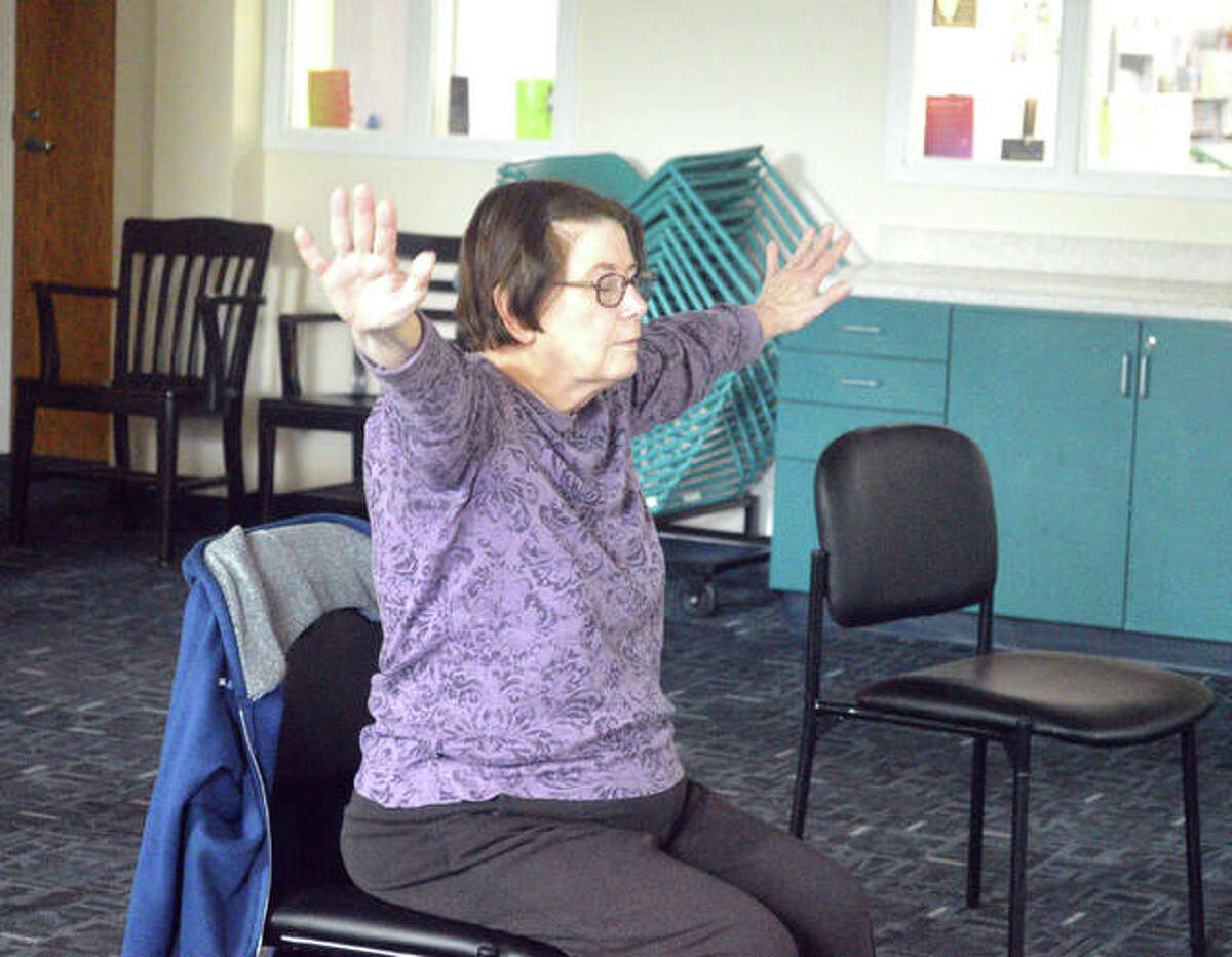 Nancy Kelley of Edwardsville participates in a chair yoga class on Monday afternoon at the Edwardsville Public Library. The class, which meets once a month, is one of many free events for seniors.