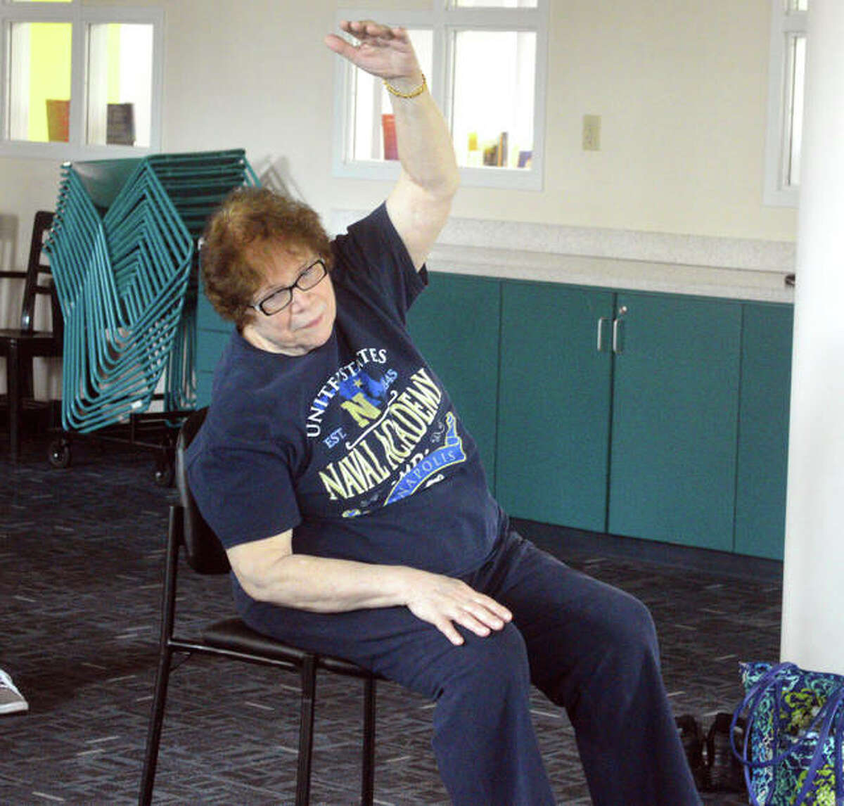 Joan Griffin of Edwardsville performs a pose during a chair yoga class Monday afternoon at the Edwardsville Public Library.
