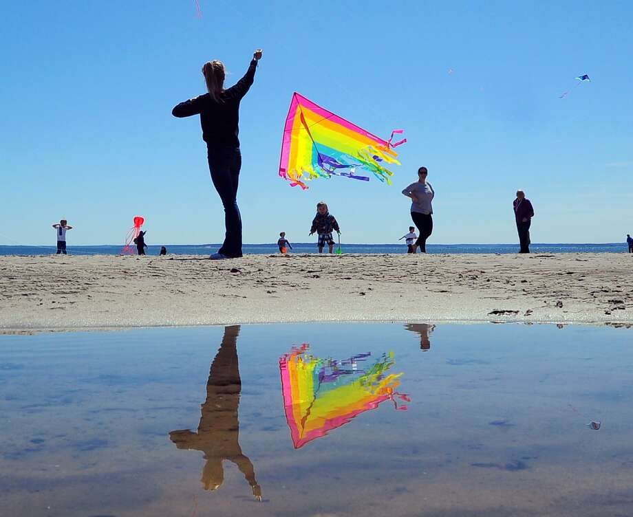 A multi-colored kite is reflected in a tidal pool during the annual Greenwich Kite Flying Festival on the beach at Greenwich Point in 2018. The event returns Saturday, April 27. Photo: Bob Luckey Jr. / Hearst Connecticut Media File Photo / Greenwich Time