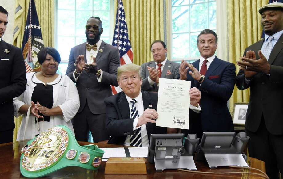 President Trump holds up a signed executive order granting a posthumous pardon for Jack Johnson, the first black heavyweight boxing champion, as boxing champion Lenox Lewis, from left, and actor Sylvester Stallone applaud in the Oval Office of the White House on May 24. A reader does not believe Trump is not racist for simply pardoning Johnson. Photo: Olivier Douliery /Bloomberg / © 2018 Bloomberg Finance LP