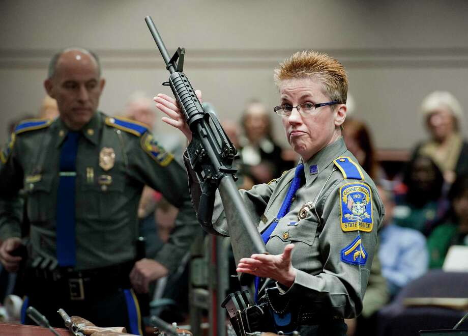 In this Jan. 28, 2013, file photo, firearms training unit Detective Barbara J. Mattson, of the Connecticut State Police, holds a Bushmaster AR-15 rifle, the same make and model used by Adam Lanza in the 2012 Sandy Hook School shooting, during a hearing at the Legislative Office Building in Hartford. Photo: Jessica Hill / Associated Press / FRE