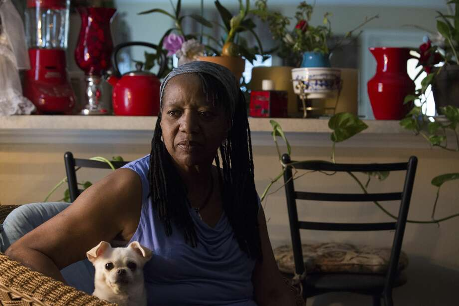 Sandra Small, 68, poses for a photograph with her dog, Sugar, at her house in Humble. Her pancreas was removed around 2012 after the doctor told her that it had stopped functioning. Small and her sons lived next to the railroad yard now owned by Union Pacific in the Kashmere Gardens neighborhood from 1974 till late 1980s. Small's oldest son, Andrew Small III, died of cancer in December when he was 52. Photo: Yi-Chin Lee/Staff Photographer