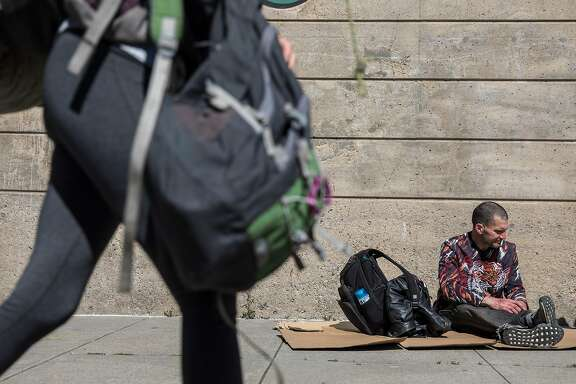 Tyson Feilzer, 40, sits on a cardboard box along Bryant Street near Main Street along the Embarcadero in San Francisco, Calif. Sunday, April 7, 2019.