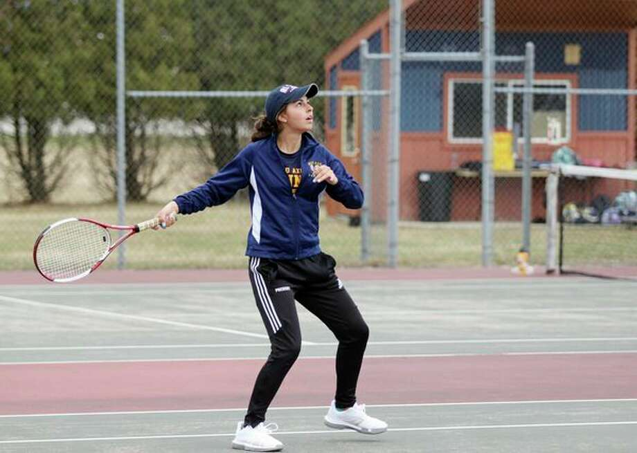 Bad Axe's No. 1 singles player, Jelena Prescott, keeps her eyes on the ball as she prepares to hit a swinging volley at the net Tuesday afternoon during a dual match against Lakers. (Mike Gallagher/Huron Daily Tribune)