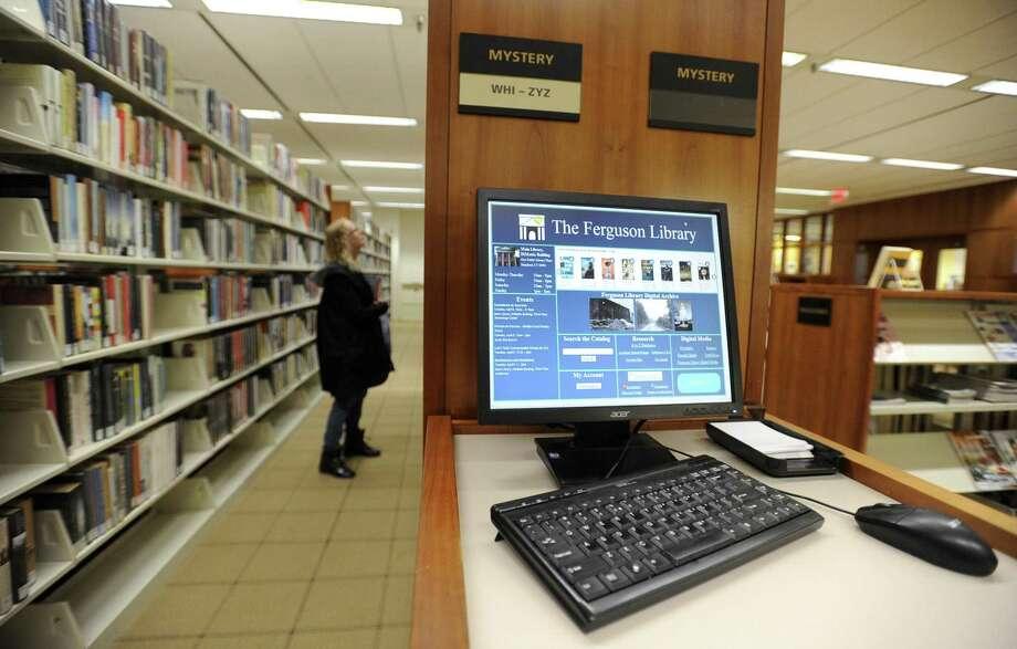 A library patron browses for a book at Ferguson Library Tuesday, April 9, 2019 in Stamford, Connecticut. Library worker union contract negotiations have broken down, mostly over retirement benefits, and talks begin with a state arbitrator on Wednesday. Photo: Matthew Brown / Hearst Connecticut Media / Stamford Advocate