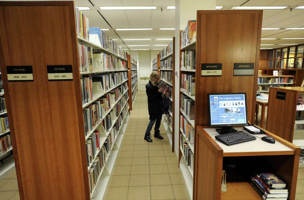 A library patron browses for a book at Ferguson Library Tuesday, April 9, 2019 in Stamford, Connecticut. Library worker union contract negotiations have broken down, mostly over retirement benefits, and talks begin with a state arbitrator on Wednesday.