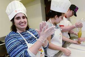 Gina Lopriore, Hillary Lipper, and Hannah Costa make crinkle cookies for Crumb Together Bakery Tuesday, Apriul 9, 2019, in the kitchen at Beth Israel Synagogue in Norwalk, Conn. Crumb Together Bakery was opened last October at Beth Israel Synagogue in Norwalk, as part of the work that the nonprofit Circle of Friends does to teach job skills to adults with disabilities.