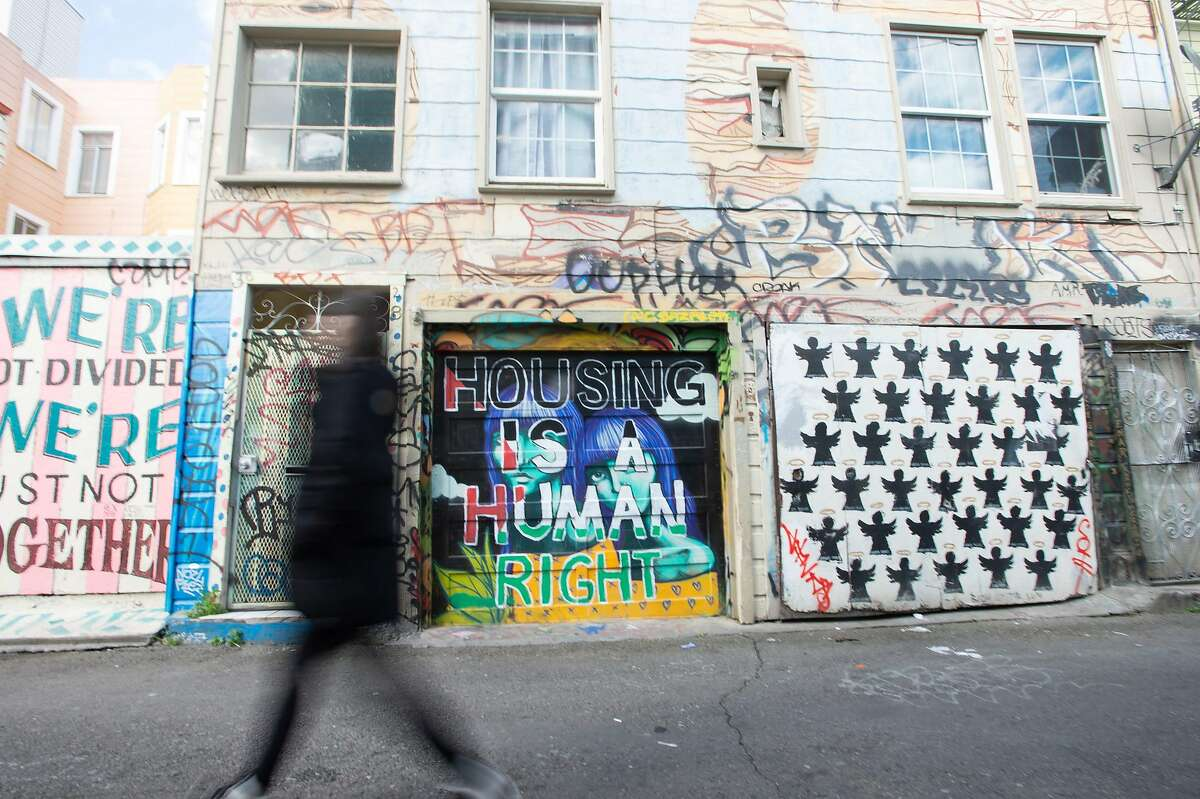 """A woman walks by a housing-related mural in San Francisco, California on February 6, 2019. - San Francisco, once home to flower power, hippies and dope, has changed dramatically: these days, it is all about Facebook, Twitter and Google, the multi-billion dollar tech giants who have turned it into one of the world's most expensive cities to live in. Average monthly rent for a two-room apartment in the city by the bay now runs to $3,700, the highest in the United States. And a household of four with annual earnings of less than $117,400 is officially officially considered """"low income."""" """"We see now a kind of homelessness that did not occur before, people who work, that is new, said Cary McClelland, author of the 2018 book """"Silicon City"""" which examines how the city has changed. (Photo by Josh Edelson / AFP)JOSH EDELSON/AFP/Getty Images"""