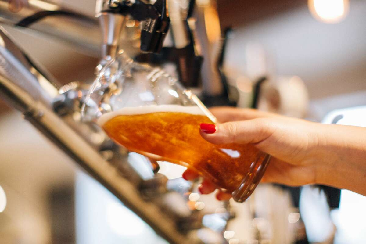 Woman pouring a glass of beer. Close-up on the hand and tap.
