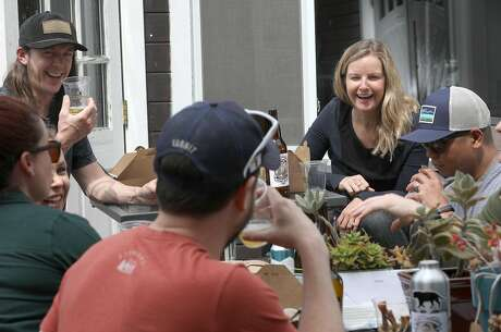 Field and sports marketing manager Michael McSherry (left) and founder and CEO Caitlin Landesberg (right) beer taste with the staff on the deck at Sufferfest's treehouse-like headquarters in the Marina District. Photo: Liz Hafalia / The Chronicle
