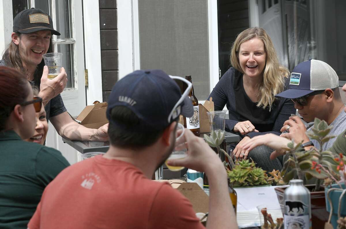 Field and sports marketing manager Michael McSherry (back left) and founder and CEO Caitlin Landesberg (back right) beer taste with the rest of the staff on the deck of Sufferfest headquarters on Monday, April 8, 2019, in San Francisco, Calif.