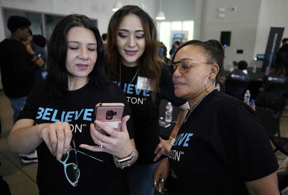 AT&T employees Anna Garcia, left, Evelynn Contreras, and Vonda Maltie, right, look at cellphone photos during an event at BakerRipley East Aldine Campus announcing an investment in Houston and the Complete Communities program by the company on April 9, 2019. Photo: Melissa Phillip, Houston Chronicle / Staff Photographer / © 2019 Houston Chronicle