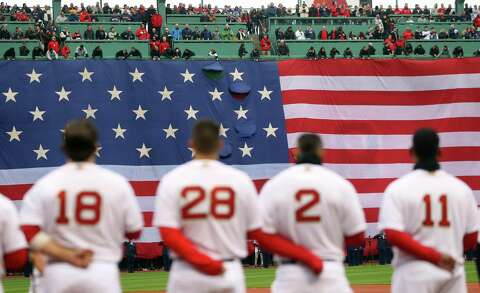 d53bb20fdd64de  p The Boston Red Sox stand for the national anthem before their home opener