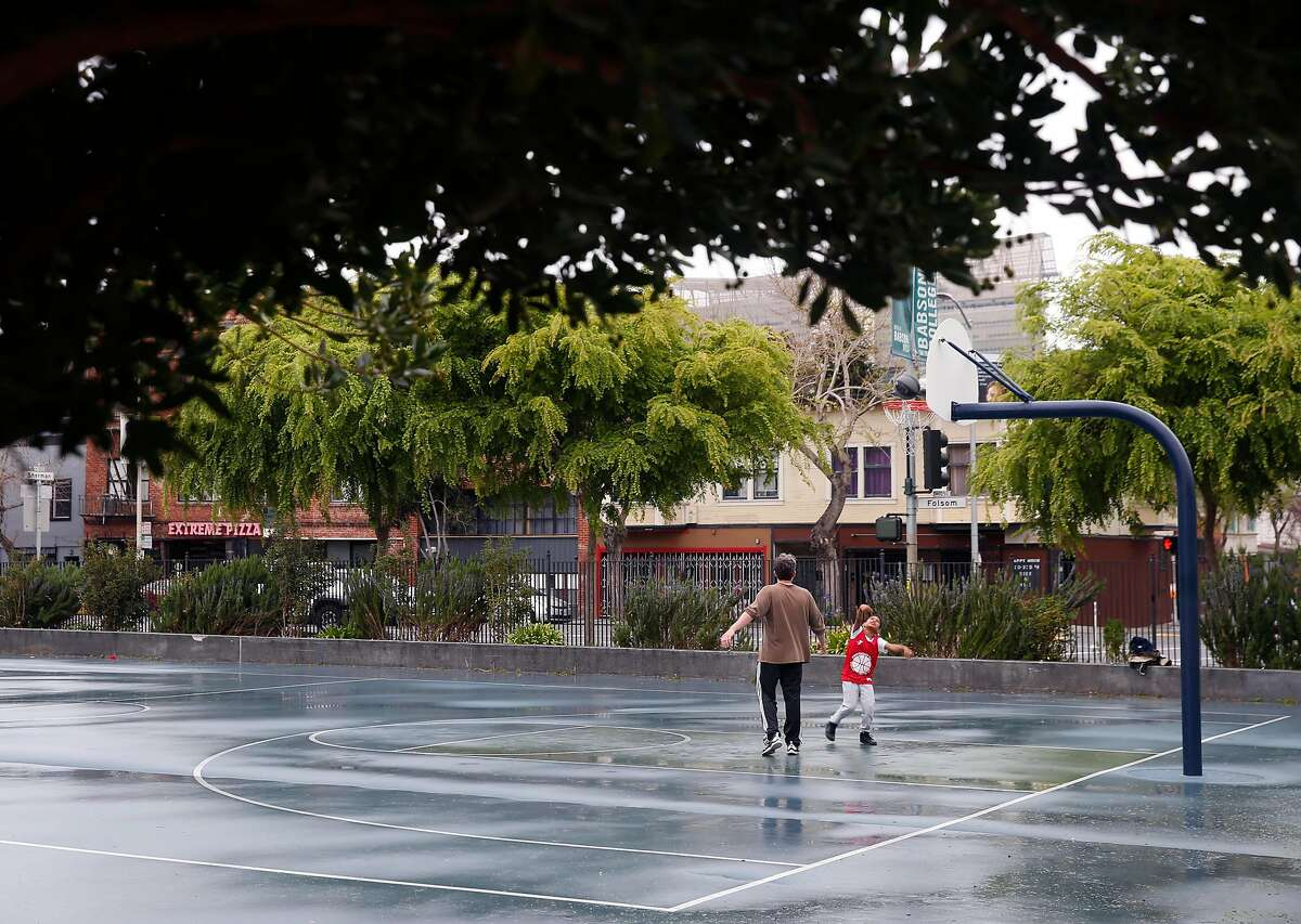 Neighbors play basketball at Victoria Manalo Draves Park in San Francisco, Calif. on Saturday, April 6, 2019 across the street from buildings on Folsom Street (background) that may be razed for revelopment. Neighbors are concerned that a planned seven story residential project constructed at Folsom and Russ streets would create shadows on the park.