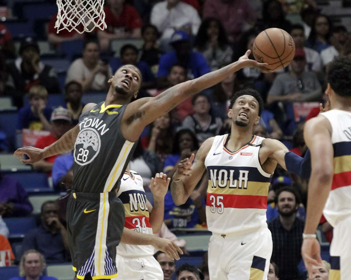 Golden State Warriors forward Alfonzo McKinnie (28) reaches for a rebound over New Orleans Pelicans forward Christian Wood (35) in the first half of an NBA basketball game in New Orleans, Tuesday, April 9, 2019. (AP Photo/Scott Threlkeld)