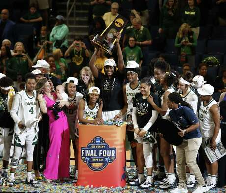 The Baylor women's team raises the championship trophy after defeating Notre Dame 82-81 on Sunday night.