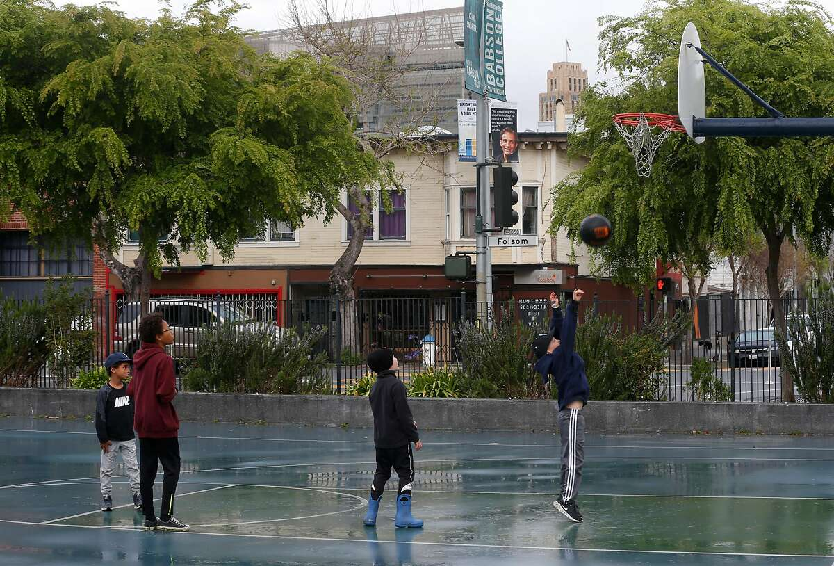 Kids play basketball at Victoria Manalo Draves Park in San Francisco, Calif. on Saturday, April 6, 2019 across the street from buildings on Folsom Street (background) that may be razed for revelopment. Neighbors are concerned that a planned seven story residential project constructed at Folsom and Russ streets would create shadows on the park.