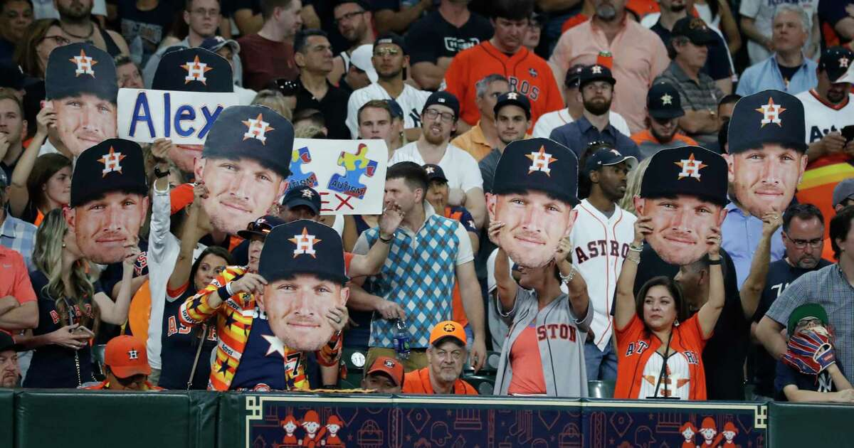 Fans of Houston Astros Alex Bregman hold up his big head during the eighth inning of an MLB game at Minute Maid Park, Tuesday, April 9, 2019, in Houston.