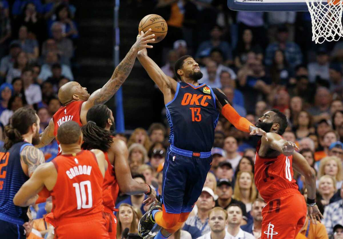 Houston Rockets forward P.J. Tucker, left, reaches up to block a shot by Oklahoma City Thunder forward Paul George (13) as George shoots between Tucker and James Harden (13) during the first half of an NBA basketball game Tuesday, April 9, 2019, in Oklahoma City. (AP Photo/Sue Ogrocki)