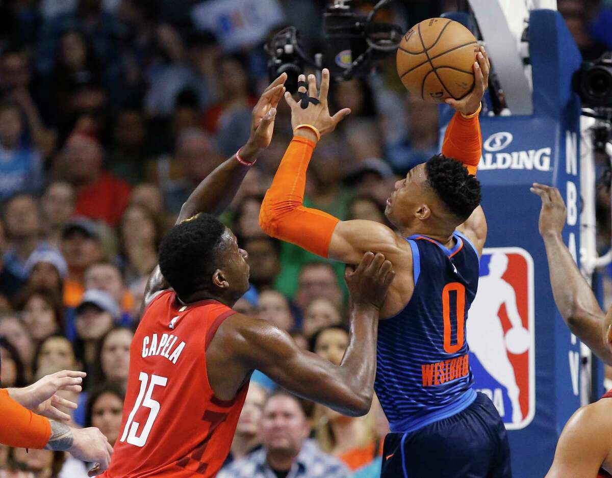 Oklahoma City Thunder guard Russell Westbrook (0) shoots in front of Houston Rockets center Clint Capela (15) during the first half of an NBA basketball game Tuesday, April 9, 2019, in Oklahoma City. (AP Photo/Sue Ogrocki)