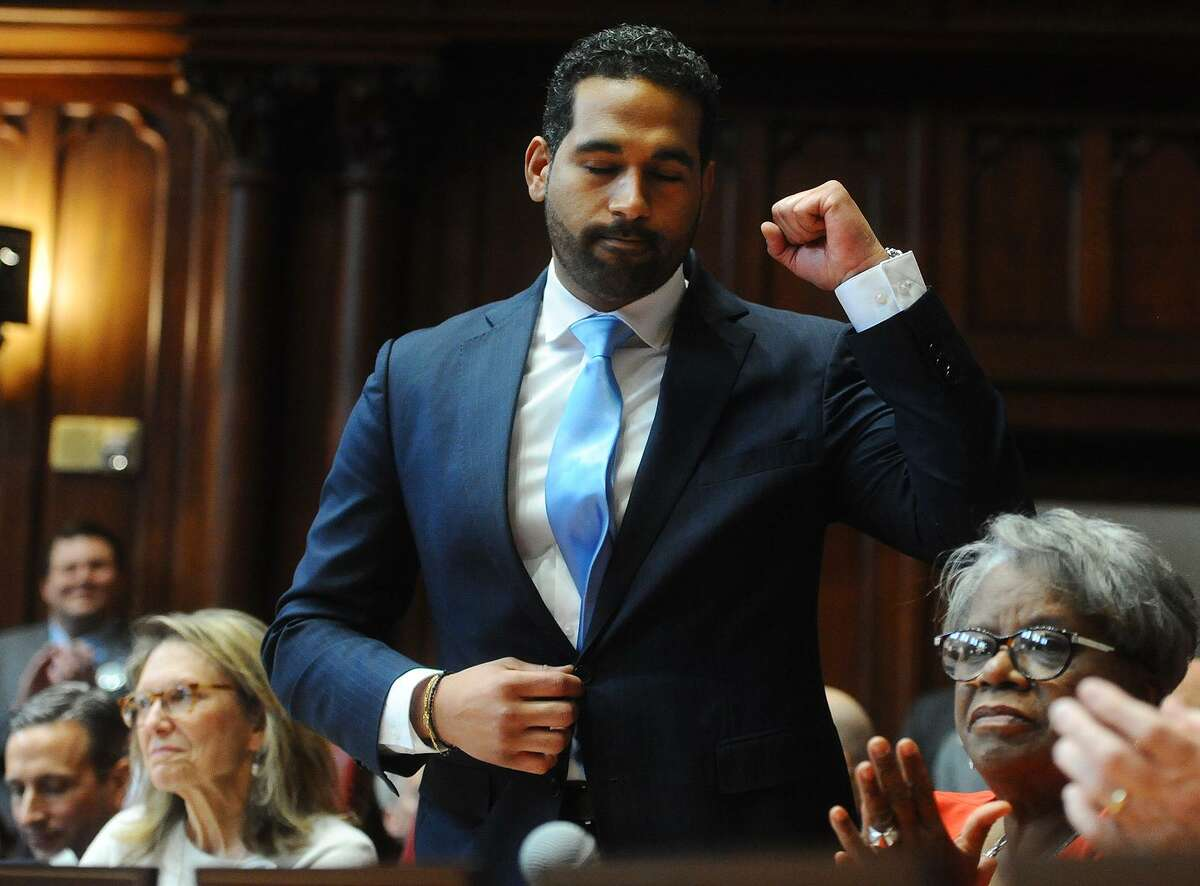 State Sen. Dennis Bradley, D-Bridgeport, pumps a fist after being introduced during the opening session of the senate in January.