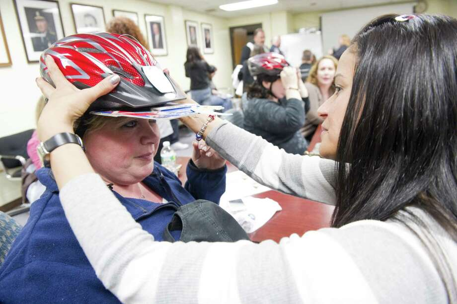Volunteer Martha Kovacs fits a helmet to Cindi Gioia as the two learn how to fit helmets properly during a training session at the Stamford Police Department, Thursday night in Stamford, Conn., April 26, 2012. Saturday April 28 from 9AM-1PM at the Fairway Market the Stamford Police Association will hold the 18th annual Timothy Coppola Memorial Bike Helmet Giveaway for children ages 4-16. A limited number of toddler size helmets will also be available. This year's helmet giveaway will also include a bike rodeo and K-9 demonstration. Timmy Coppola sustained a traumatic brain injury as a result of a bicycle accident on Aug. 30, 1992, he was not wearing a helmet. Over the years the event has given away 25,000 helmets. Photo: Keelin Daly / Keelin Daly / Stamford Advocate