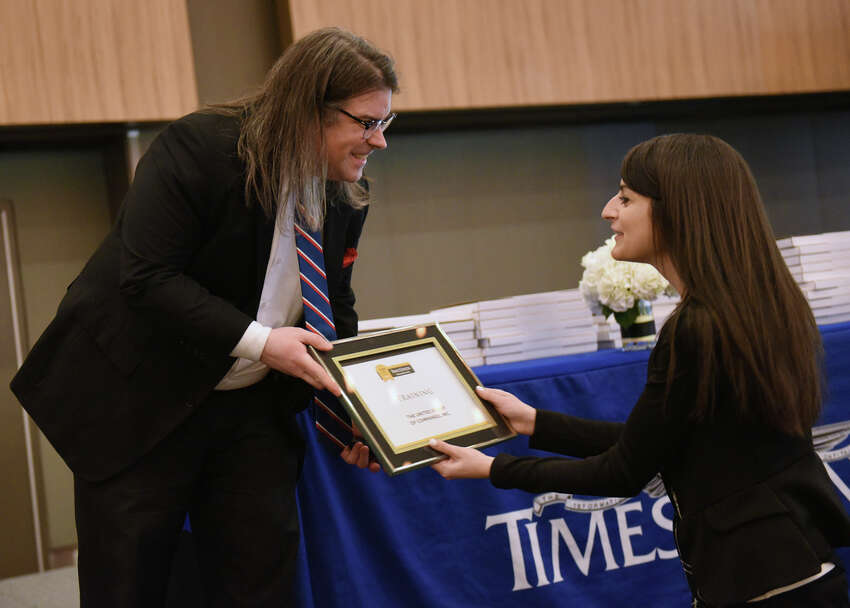 Times Union's Greg Stapleton hands Michaela Gabriele, a human resource manager at The United Group of Companies, Inc., a Training Award during the Annual Top Workplaces event at the Albany Capital Center on Tuesday April 9, 2019 in Albany, N.Y. (Lori Van Buren/Times Union)