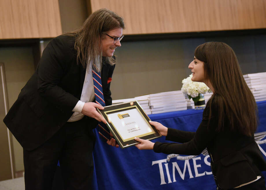 Times Union's Greg Stapleton hands Michaela Gabriele, a human resource manager at The United Group of Companies, Inc., a Training Award during the Annual Top Workplaces event at the Albany Capital Center on Tuesday April 9, 2019 in Albany, N.Y. (Lori Van Buren/Times Union) Photo: Lori Van Buren, Albany Times Union / 20046647A