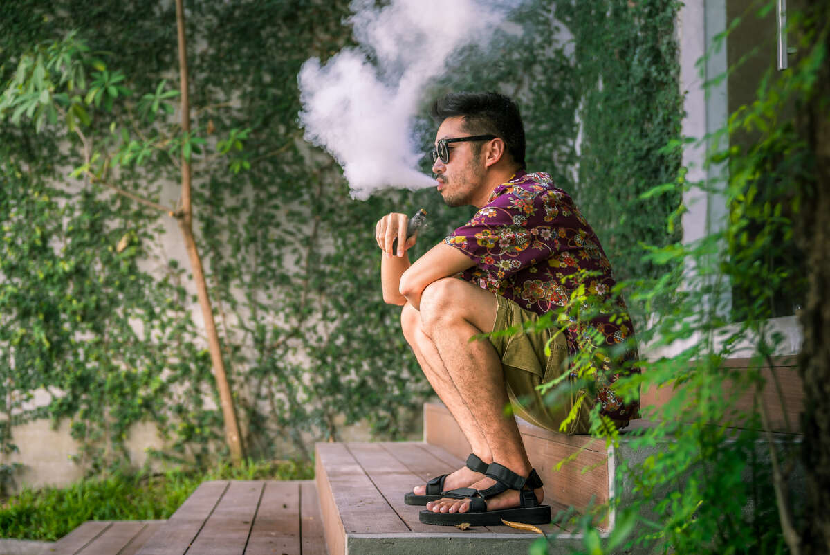 Man Using An Electric Cigarette A image of a young adult male has a cloud of nicotine vapor 'smoke' pouring from his mouth. Vape smoking, or 'vaping' is growing in popularity, as well as falling under stricter state and governmental regulations.