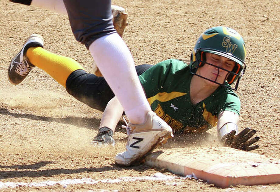 Southwestern's Josie Bouillon dives back to first base ahead of the throw to avoid a double play in a lineup Saturday at Alton High in Godfrey. Bouillon had four hits and four RBIs Tuesday in the Piasa Birds' SCC victory at Vandalia. Photo: Greg Shashack / The Telegraph