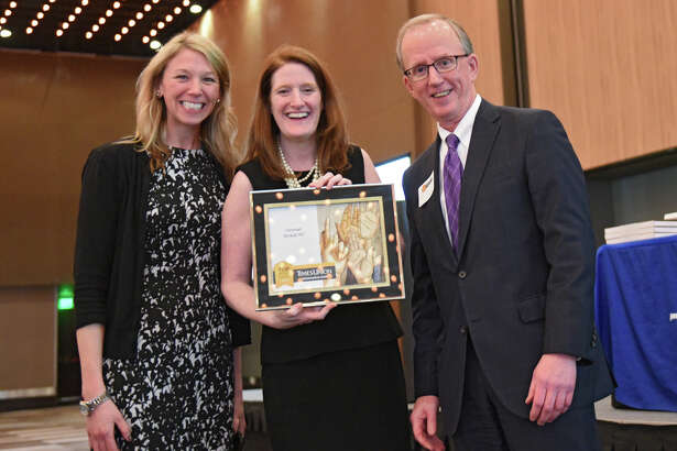 Times Union's Tom Eason, right, presented Brittany MacCrea, left, and Janet Silver of Hinman Straub P.C. an award during the Annual Top Workplaces event at the Albany Capital Center on Tuesday April 9, 2019 in Albany, N.Y. (Lori Van Buren/Times Union)